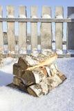 Leña del abedul en la nieve contra la perspectiva de una cerca de madera Fotografía de archivo
