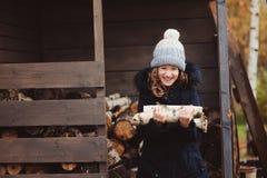 Leña feliz de la cosecha de la muchacha del niño de la vertiente en invierno Imagenes de archivo