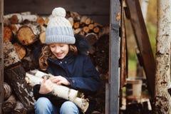 Leña feliz de la cosecha de la muchacha del niño de la vertiente en invierno Fotografía de archivo libre de regalías