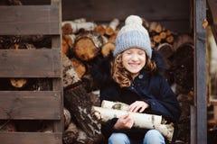 Leña feliz de la cosecha de la muchacha del niño de la vertiente en invierno Imagen de archivo
