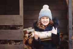Leña feliz de la cosecha de la muchacha del niño de la vertiente en invierno Fotos de archivo