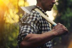 Leñador en el bosque con un hacha Imagen de archivo libre de regalías