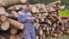 Leñador o carpintero del trabajador con un manojo grande de dinero cerca de una pila de registros, madera aserrada Concepto de ac almacen de video
