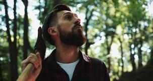 Leñador que se coloca con su hacha en el bosque, mirando alrededor Retrato del hombre barbudo hermoso con el hacha almacen de metraje de vídeo