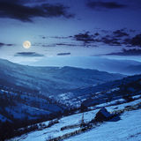 Leñera en la ladera en montañas del invierno en la noche Fotos de archivo