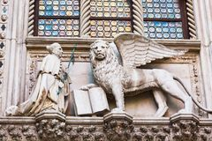 León con alas y un sacerdote Detail del palacio Palazzo Ducale del ` s del dux en Venecia, Italia imagenes de archivo
