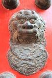 León de bronce chino en la puerta roja Foto de archivo