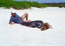 León y turista de mar de las Islas Gal3apagos imagen de archivo libre de regalías