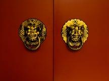Leões dourados na porta vermelha Fotografia de Stock Royalty Free