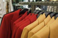 Le ` à la mode s d'hommes et le ` s de femmes enduisent sur des cintres dans un magasin d'habillement moderne photos libres de droits