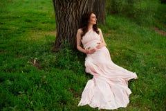 Le årigt vila för gravid kvinna 25-29 vid sjön Posera utomhus motherhood maternity arkivbild
