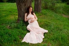 Le årigt vila för gravid kvinna 25-29 vid sjön Posera utomhus motherhood maternity fotografering för bildbyråer