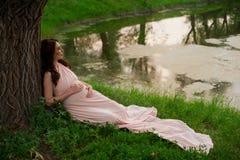 Le årigt vila för gravid kvinna 25-29 vid sjön Posera utomhus motherhood maternity royaltyfria bilder