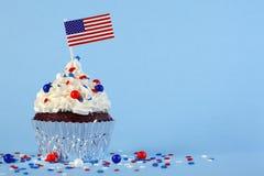 le 4ème du petit gâteau de juillet avec le drapeau, arrose Images libres de droits