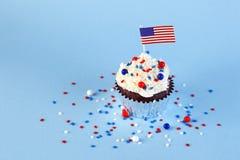 le 4ème du petit gâteau de juillet avec le drapeau, arrose Photo libre de droits