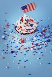 le 4ème du petit gâteau de juillet avec le drapeau, arrose Photographie stock libre de droits