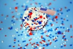 le 4ème du petit gâteau de juillet avec le drapeau, arrose Image libre de droits