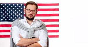 le 4ème juillet Jeune homme de sourire sur le fond de drapeau des Etats-Unis Photo stock