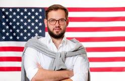 le 4ème juillet Jeune homme de sourire sur le fond de drapeau des Etats-Unis Images stock