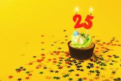 le 25ème petit gâteau d'anniversaire avec la bougie et arrose Photos stock