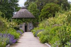 Le 19ème siècle a couvert de chaume autour de la maison entourée par de beaux lits de fleur et chemins de gravier dans le jardin  Image stock