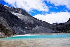 Le acque calme del lago, la neve hanno ricoperto la montagna Immagine Stock