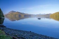 Le acque calme della baia di Grice riflettono l'isola e la barca di Meares Fotografie Stock Libere da Diritti