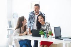 Le affärsfolk som delar deras idéer i modernt kontor arkivbilder