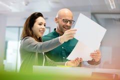 Le affärsfolk som i regeringsställning diskuterar över skrivbordsarbete Arkivbild