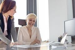 Le affärskvinna- och kvinnligchefen som i regeringsställning granskar projekt Royaltyfria Bilder