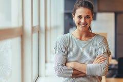 Le affärskvinnaanseende med korsade armar fotografering för bildbyråer