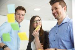 Le affärskvinnan By Colleagues Looking på anmärkningar som klibbas på Gl royaltyfri foto