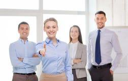 Le affärskvinnan i regeringsställning med laget på baksida Arkivfoto