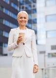 Le affärskvinnan med den pappers- koppen utomhus Royaltyfri Bild