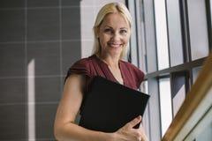 Le affärskvinnan med en mapp i regeringsställning royaltyfria bilder