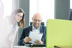 Le affärskvinnan och affärsmanläseboken på kontoret Royaltyfri Fotografi