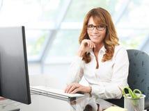 Le affärskvinnan på kontorsskrivbordet med en dator Arkivbild