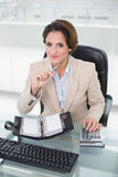 Le affärskvinnan som använder räknemaskinen och dagboken som ser kameran Fotografering för Bildbyråer