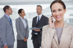 Le affärskvinnan som kallar medan kollegor som tillsammans talar Arkivfoto
