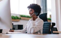 Le affärskvinnan som talar med klienten över telefonen royaltyfri fotografi