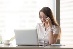 Le affärskvinnan som talar på telefonen, medan genom att använda bärbara datorn, calli royaltyfri foto