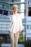 Le affärskvinnan som utanför går med mobiltelefonen Fotografering för Bildbyråer