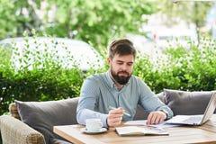 Le affärsmannen Enjoying Working i kafé arkivfoto