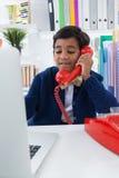 Le affärsmannen genom att använda bärbara datorn, medan tala på landlinetelefonen royaltyfri fotografi