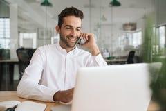 Le affärsmannen genom att använda en bärbar dator och tala på hans mobiltelefon royaltyfri bild