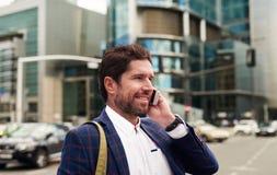 Le affärsmannen som går i staden som talar på hans mobiltelefon Arkivfoto