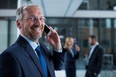 Le affärsmannen som i regeringsställning talar på korridoren för mobiltelefon Arkivbild