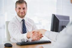 Le affärsmannen som skakar händer med en arbetare och att se för Co a Arkivbild