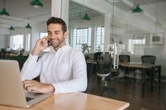 Le affärsmannen som talar på en mobiltelefon och att använda hans bärbar dator royaltyfri foto