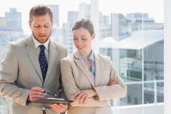 Le affärspartners som går över dokument på skrivplattan Arkivbilder